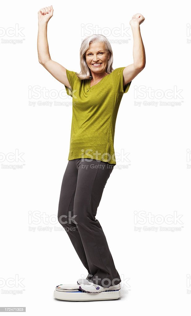 Senior woman smiling on a scale and raising hands royalty-free stock photo
