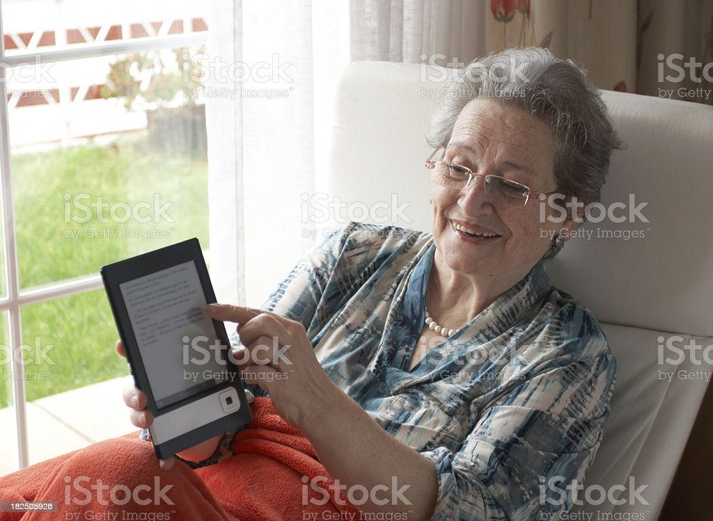 Senior woman smiling showing text in an ebook. royalty-free stock photo