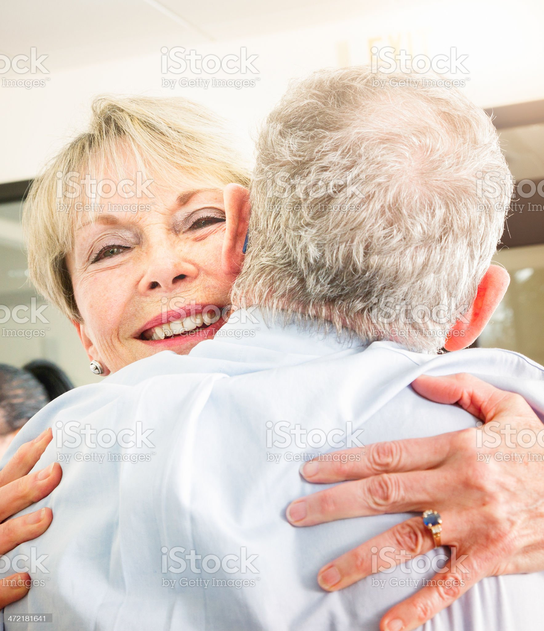 Senior woman smiling while hugging her older brother royalty-free stock photo
