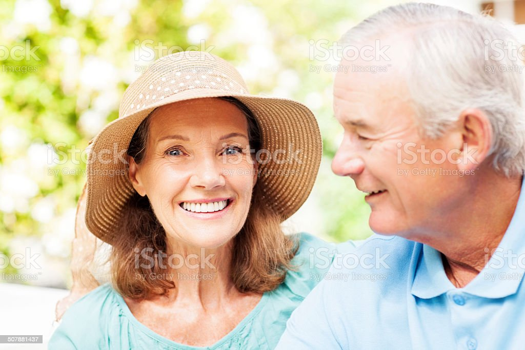 Senior Woman Smiling While Man Looking At Her In Garden royalty-free stock photo