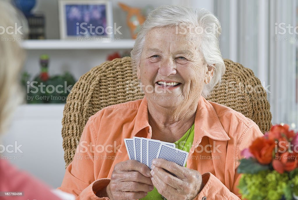 Senior Woman smiling while playing a card game royalty-free stock photo