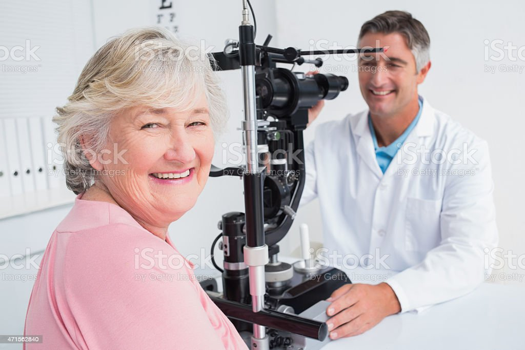 Senior woman smiling while sitting with optician stock photo