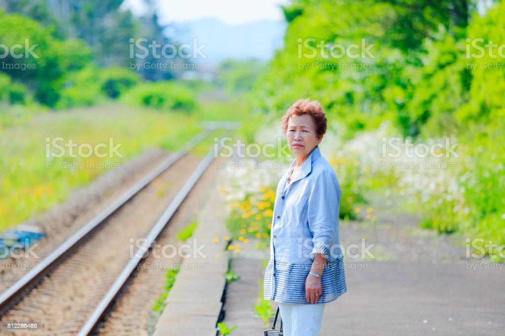 Senior woman standing at the station stock photo
