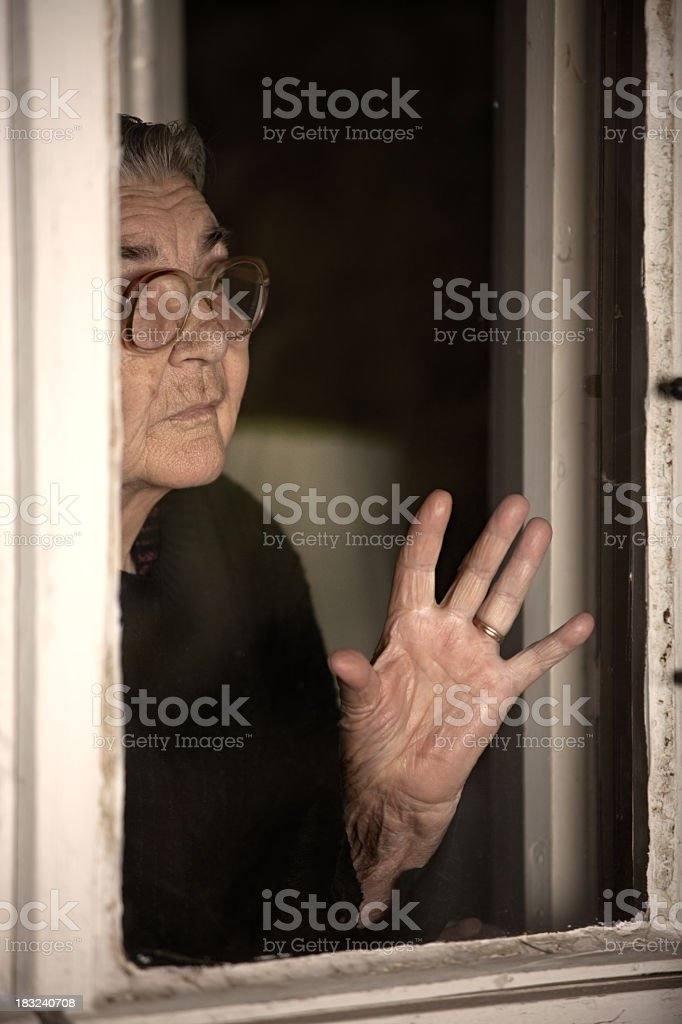 Senior woman standing by the window and looking out royalty-free stock photo