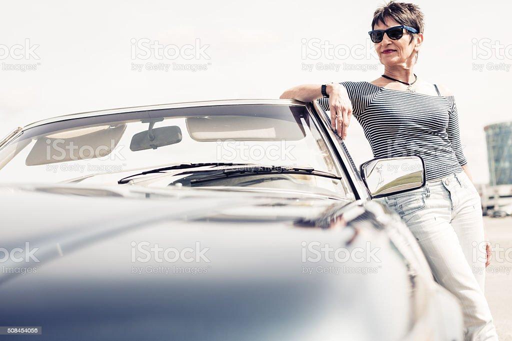 senior woman standing next to convertible classic car stock photo