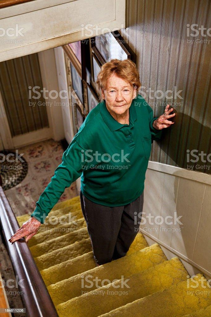 Senior woman standing on staircase stock photo