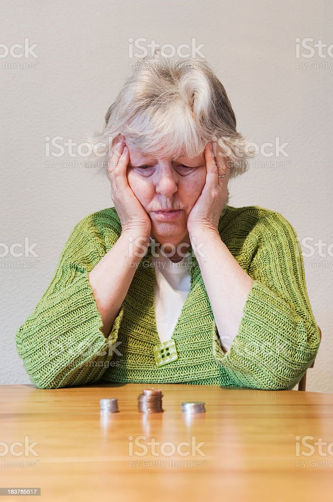 Senior woman staring at piles of coins on a wooden desk royalty-free stock photo