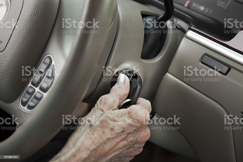 senior woman starting car with key in ignition lock stock photo