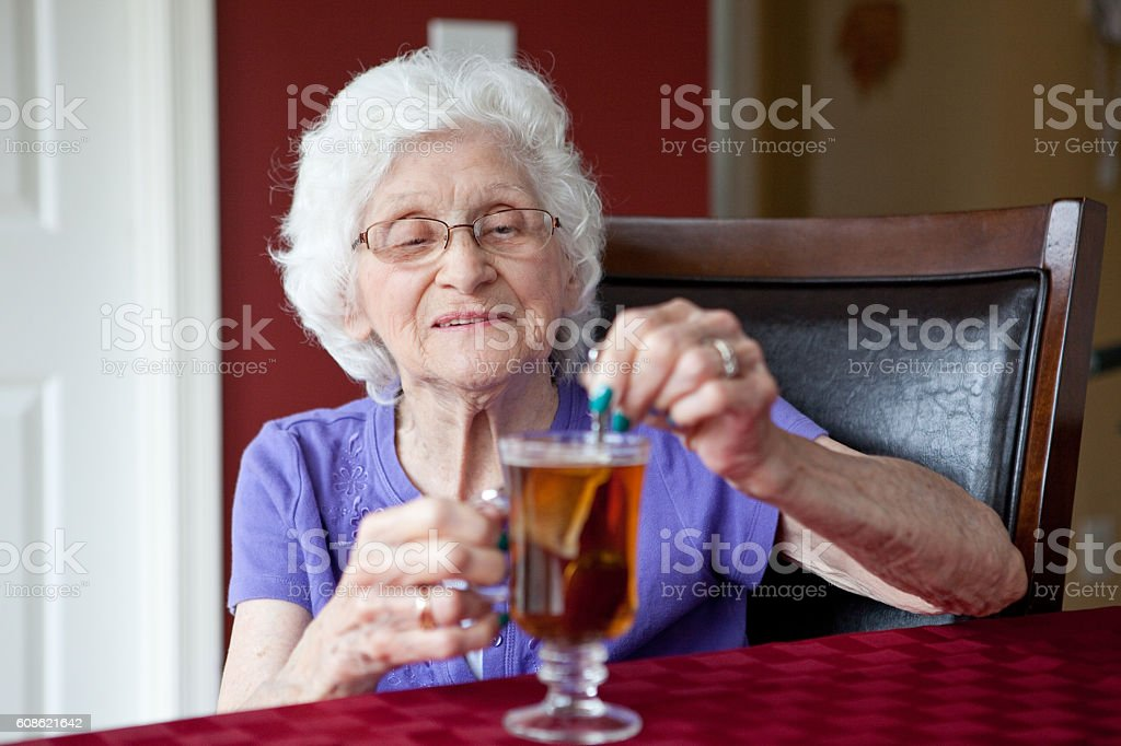 Senior Woman Stirring Cup Of Tea stock photo