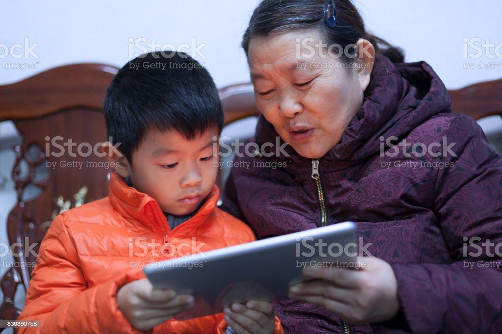 Senior woman storytelling with boy using digital tablet stock photo