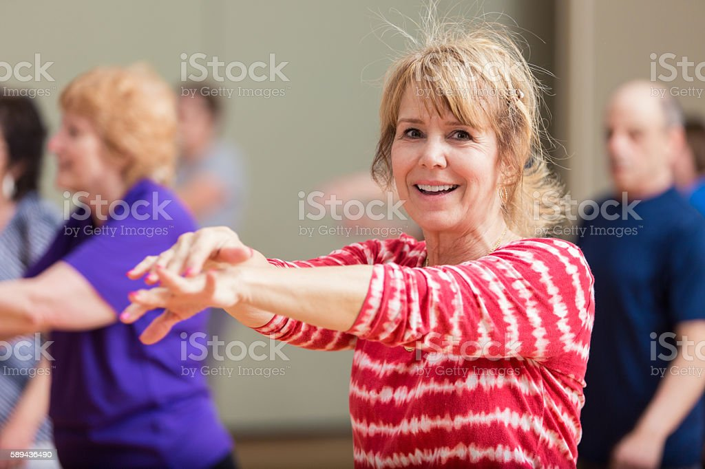 Senior woman stretches in exercise class stock photo