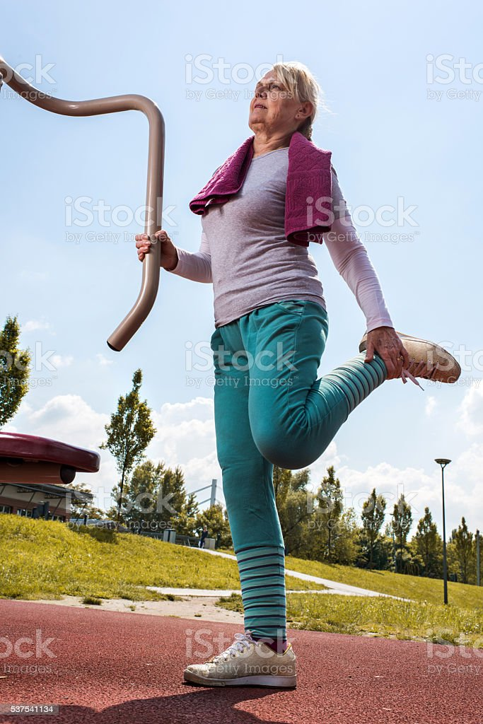 Senior woman stretching her leg at outdoor gym. stock photo
