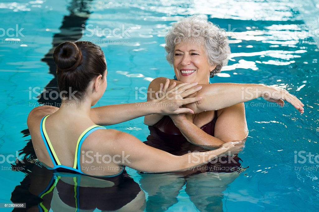 Young trainer helping senior woman in aqua aerobics. Senior retired...