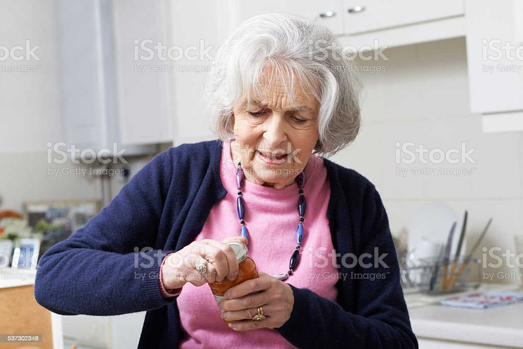Senior Woman Struggling To Take Lid Off Jar stock photo