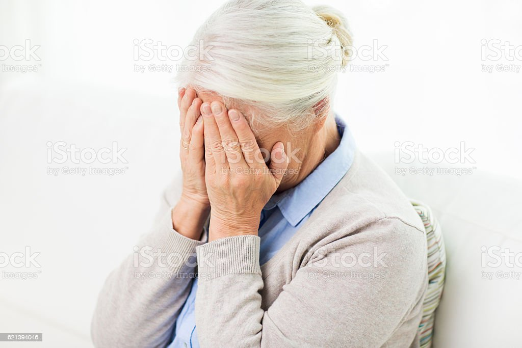 senior woman suffering from headache or grief stock photo