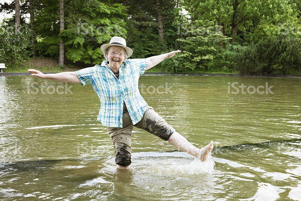senior woman summer fun in pond royalty-free stock photo
