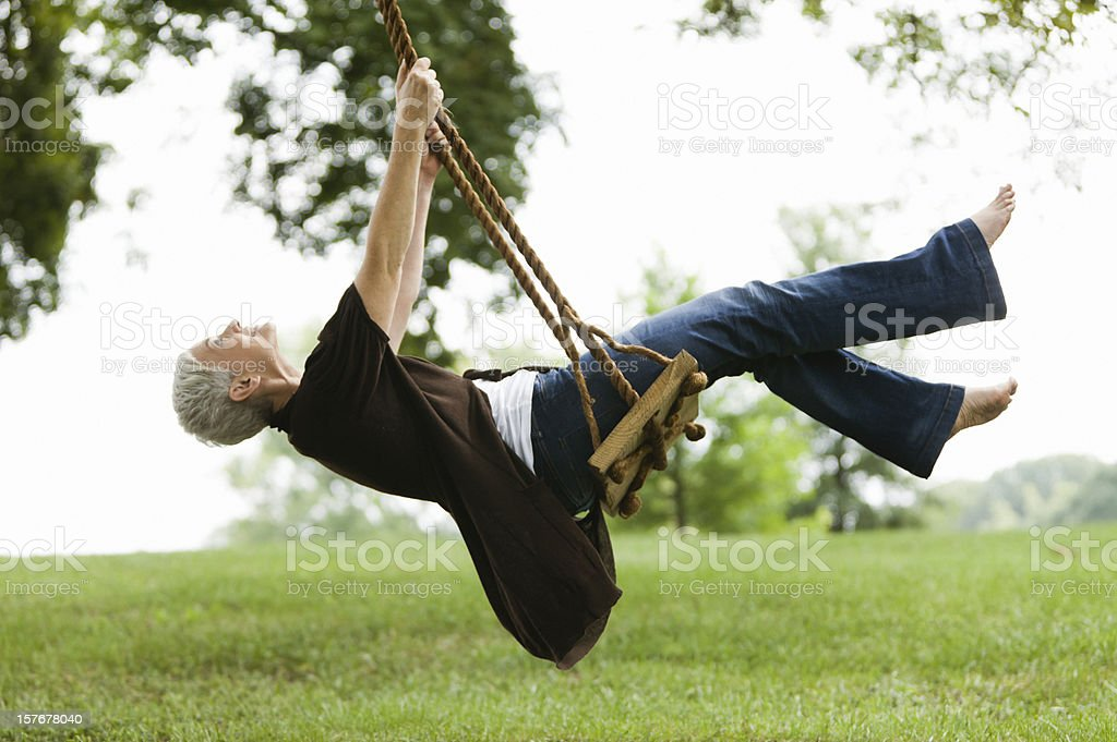Senior Woman Swinging Under a Tree stock photo