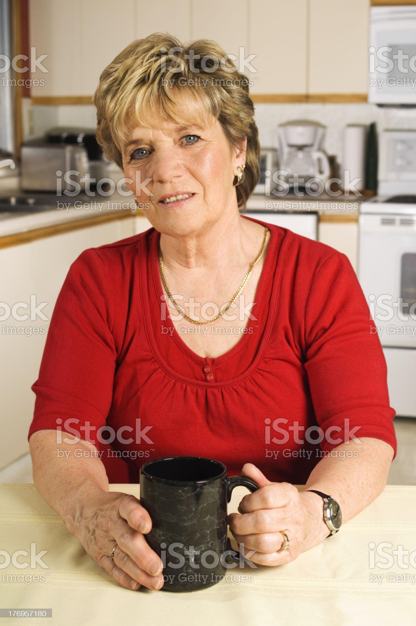 Senior woman taking a coffee break in her kitchen royalty-free stock photo