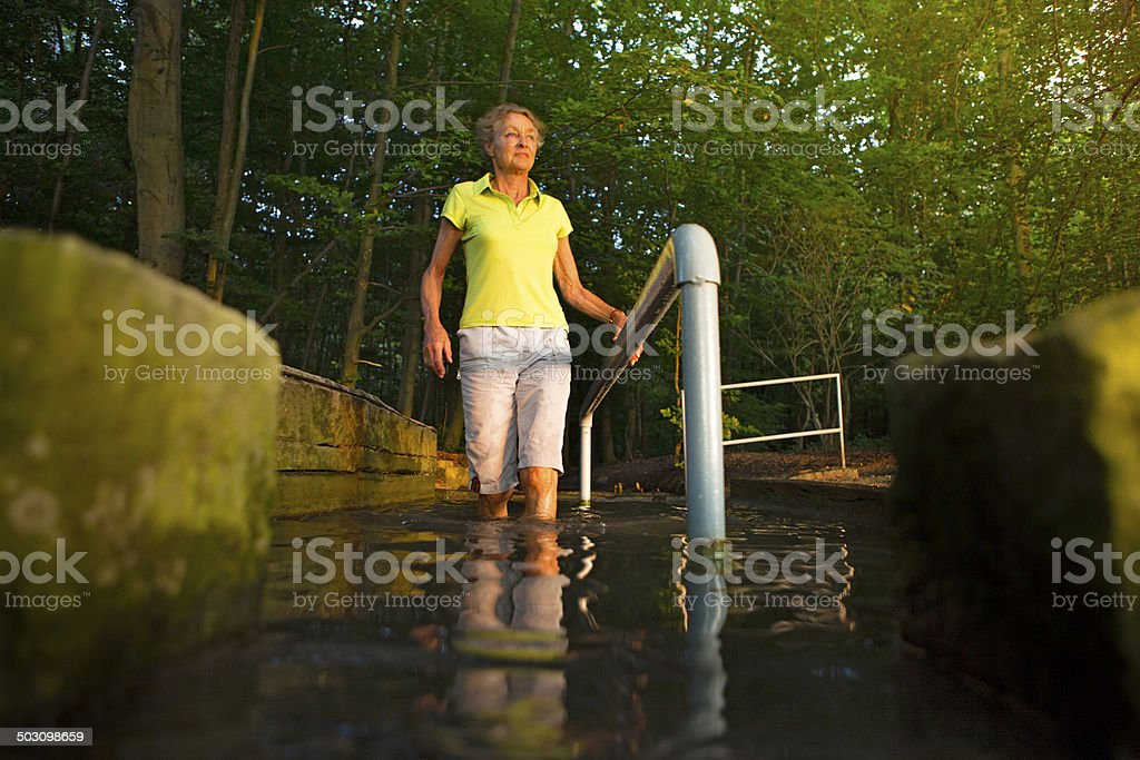 senior woman taking a kneipp cur in a water basin stock photo