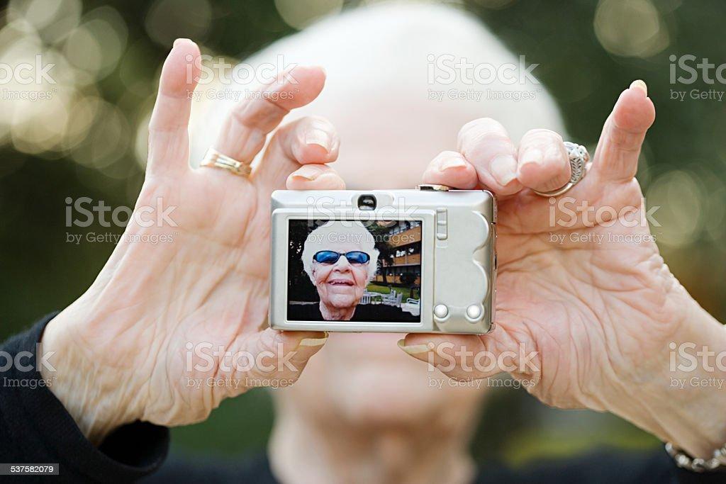 Senior woman taking a self portrait photograph stock photo
