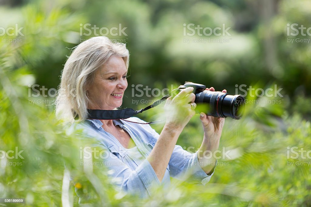 Senior woman taking photographs with camera stock photo