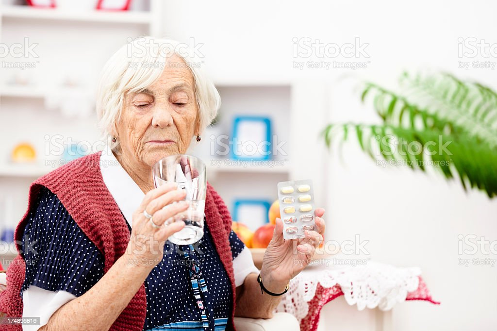 Senior woman taking pills royalty-free stock photo