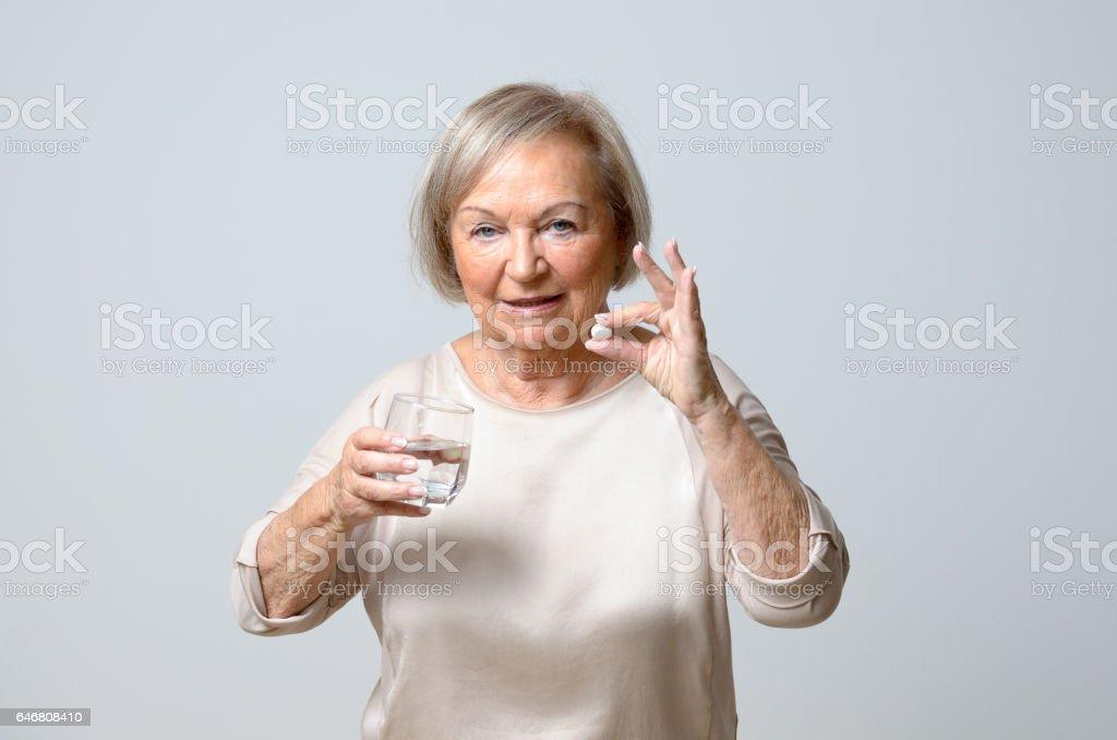 Senior woman taking pills stock photo