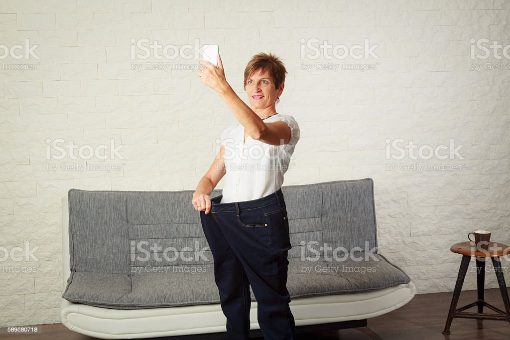 Senior woman taking selfie, showing her weight loss stock photo