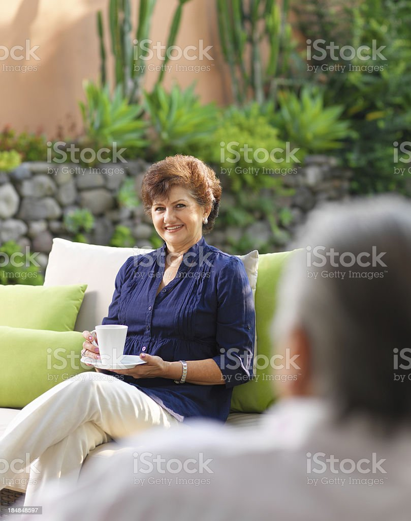 Senior woman talking and drinking coffee royalty-free stock photo