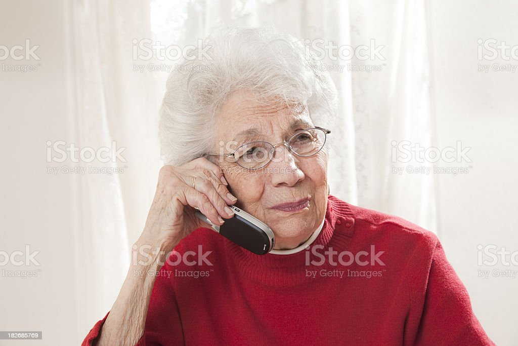 senior woman talking on phone with troubled facial expression stock photo