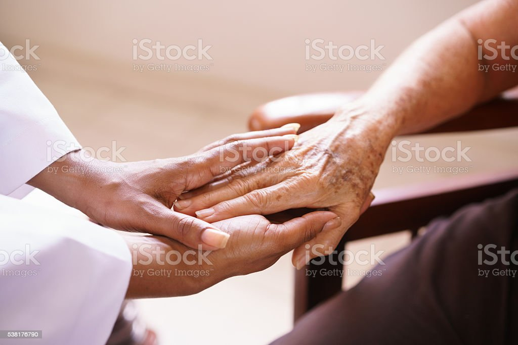 Senior Woman Talking With Black Doctor In Hospice stock photo