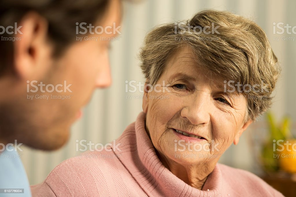 Senior woman talking with doctor stock photo
