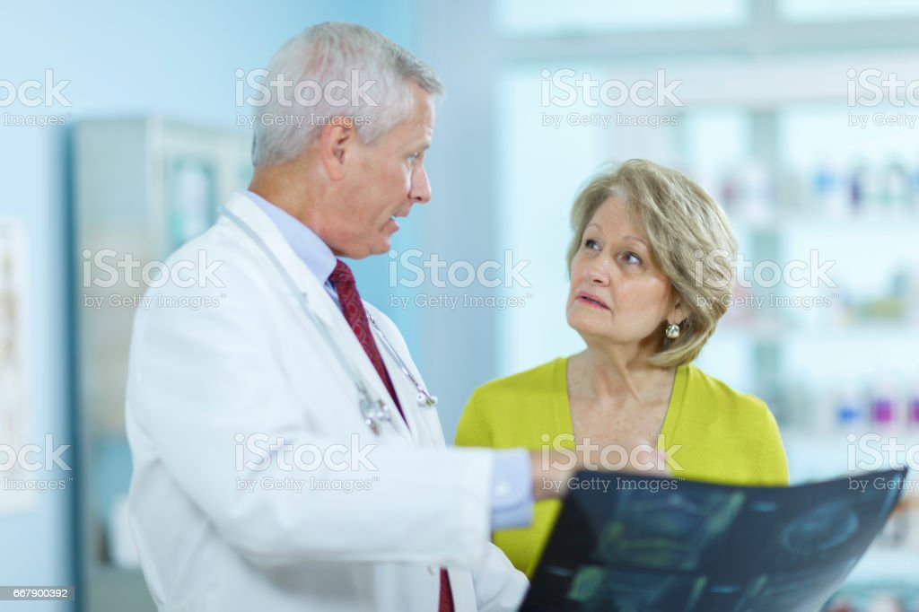Senior woman talking with doctor. stock photo