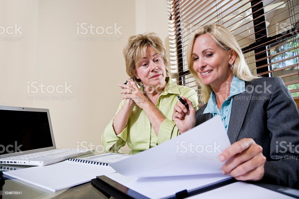 Senior woman talking with financial planner or consultant royalty-free stock photo