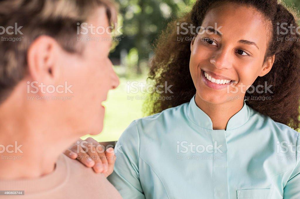 Senior woman talking with nurse stock photo