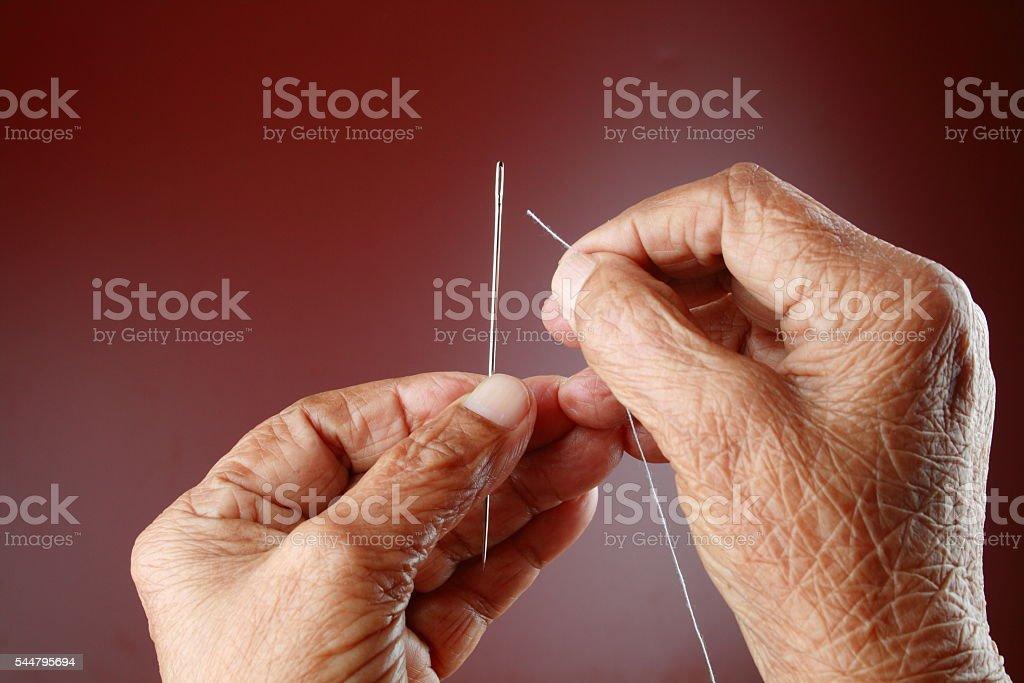 Senior woman thread a needle stock photo