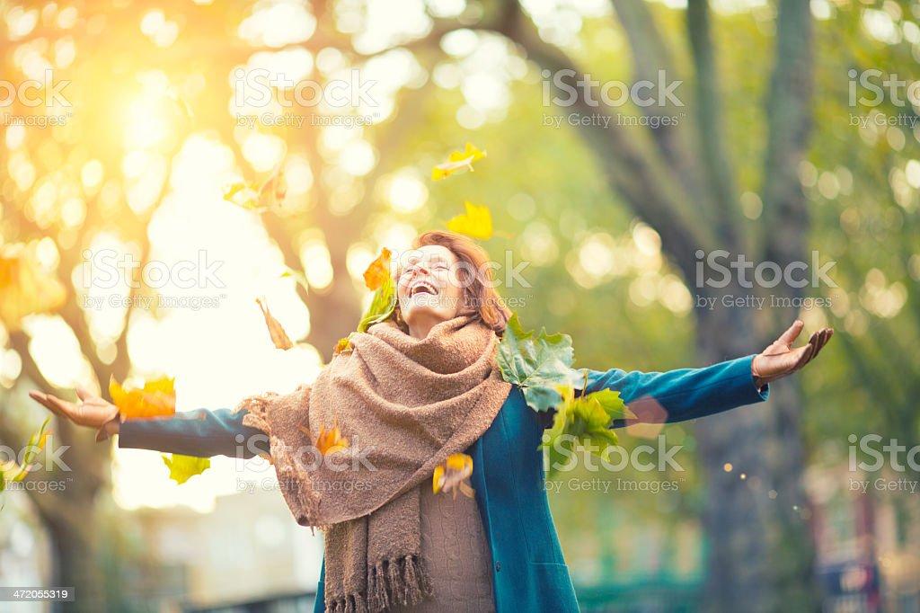 Senior Woman Throwing Maple Leaves stock photo