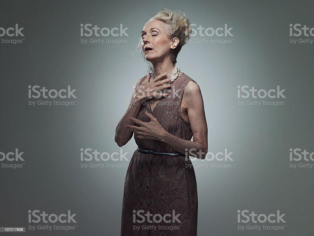 Senior woman touching chest, portrait stock photo