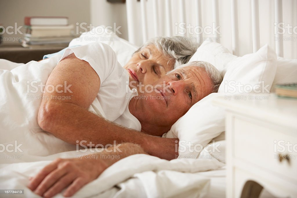 Senior Woman Tries To Be Affectionate Towards Husband In Bed stock photo