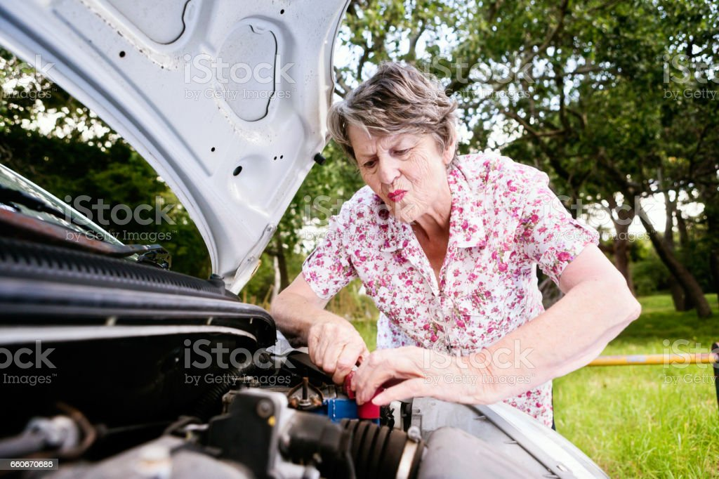 Senior woman trying in vain to fix broken-down car stock photo