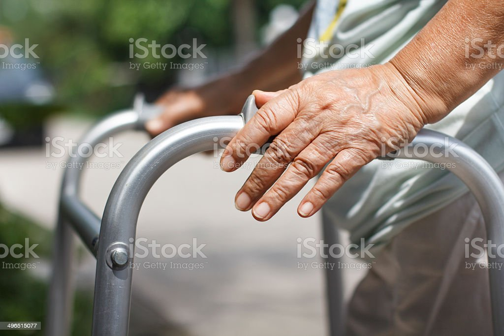 senior woman using a walker cross street stock photo