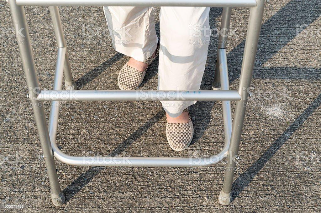 senior woman using a walker cross street. stock photo
