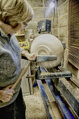 senior woman using chisel and lathe to create wooden bowl