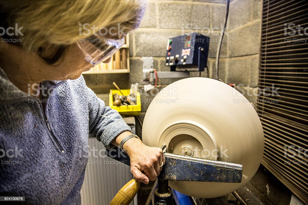 senior woman using chisel and lathe to create wooden bowl stock photo