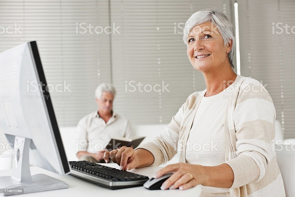 Senior woman using computer with man in the background royalty-free stock photo