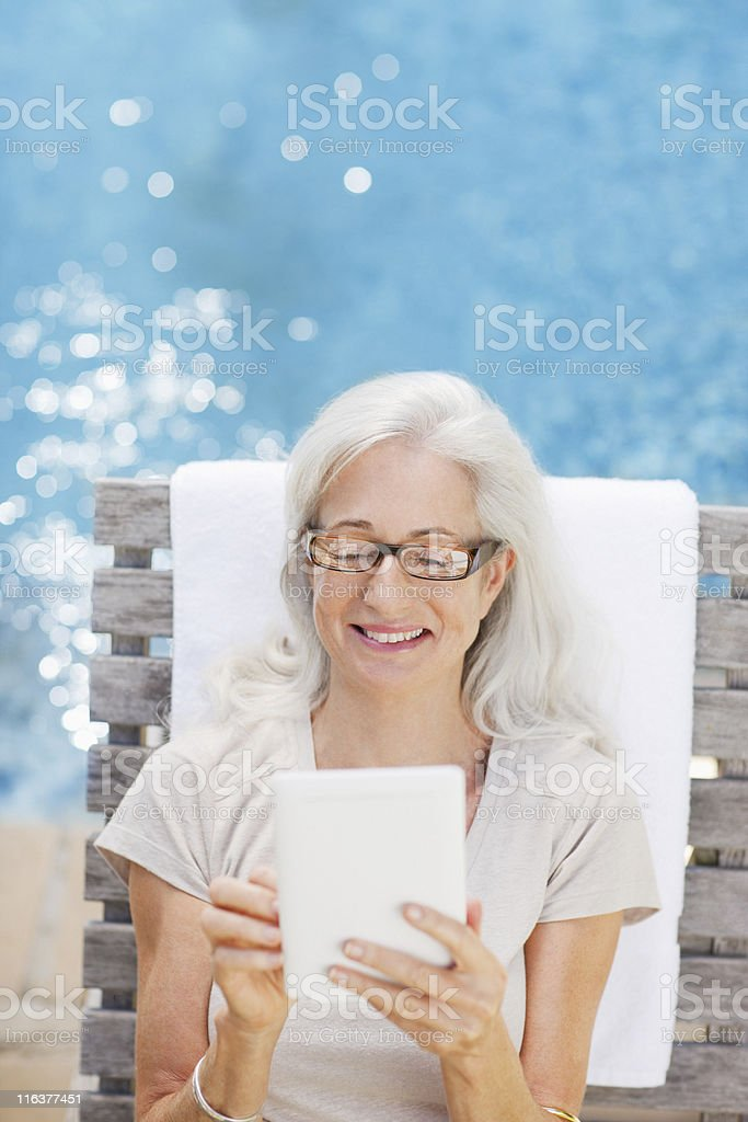 Senior woman using digital tablet poolside royalty-free stock photo