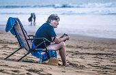 Senior Woman Using Earphone Mobile Phone Technology Beach
