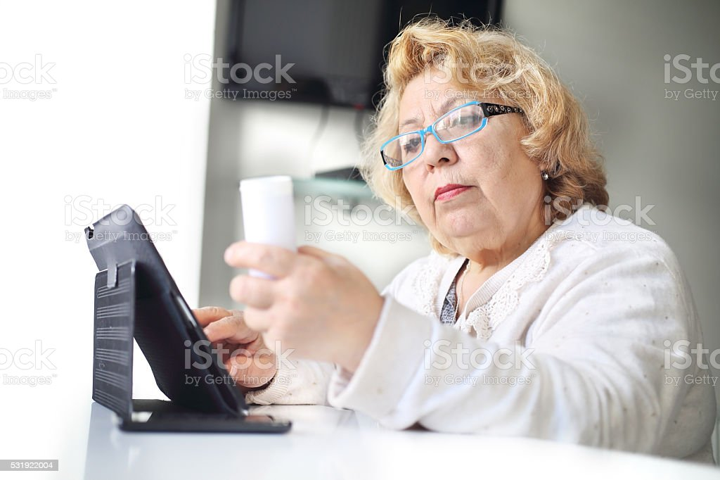 Senior woman using healthcare technology about medication stock photo