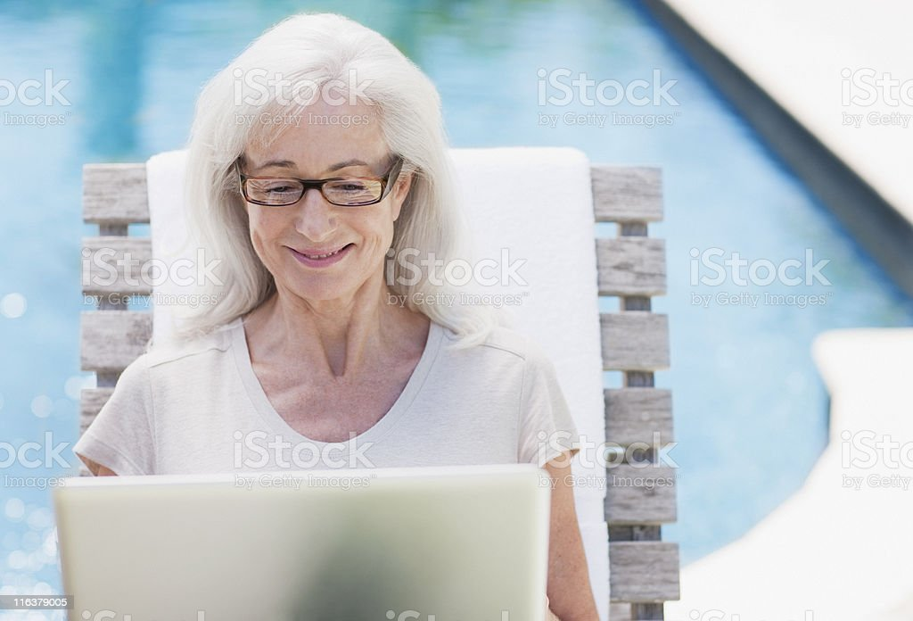 Senior woman using laptop at poolside royalty-free stock photo