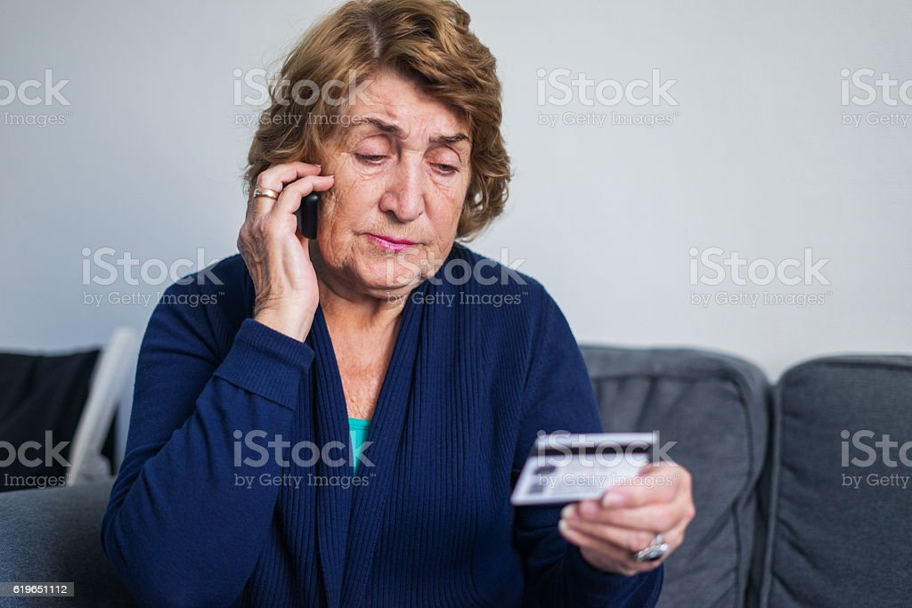 Senior woman using mobile phone while holding credit card stock photo